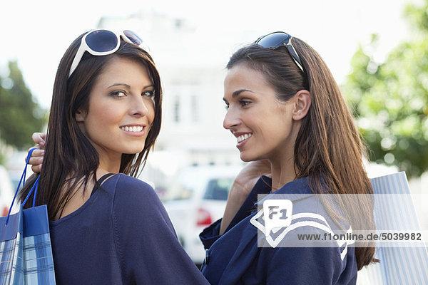 Zwei junge Frauen stehend mit Einkaufstaschen