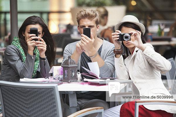 Drei junge Freunde mit elektronischen Gadgets in einem Restaurant