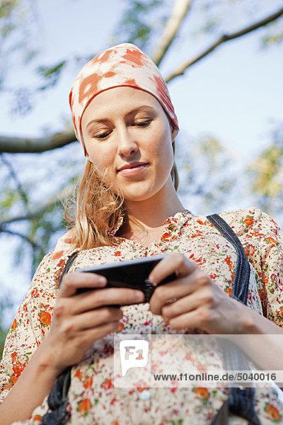 Schöne Frau SMS auf einem Handy