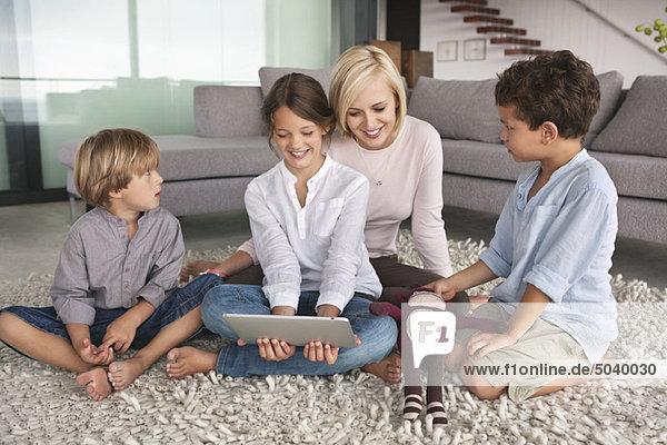 Mädchen  das ein digitales Tablett benutzt  während ihre Mutter und ihre Brüder neben ihr sitzen.