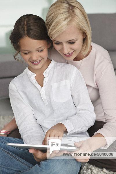 Frau unterstützt ihre Tochter bei der Verwendung eines digitalen Tabletts
