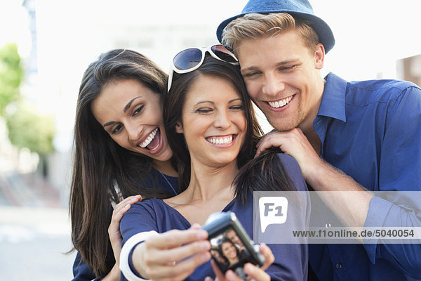 Three young people taking photo of themselves