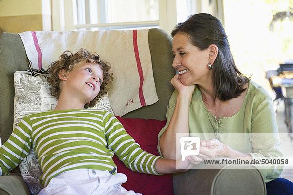 Großmutter und kleiner Junge sitzen zusammen zu Hause.
