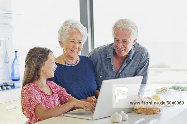 Mädchen  das einen Laptop benutzt  während ihre Großeltern sie in der Küche anschauen.