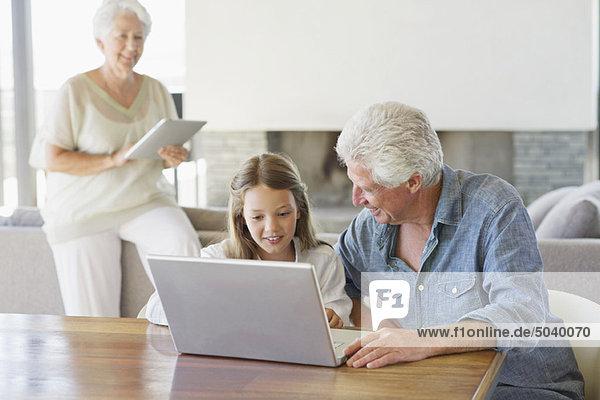 Mann  der mit seiner Enkelin und seiner Frau einen Laptop benutzt und im Hintergrund an einem digitalen Tablett arbeitet.
