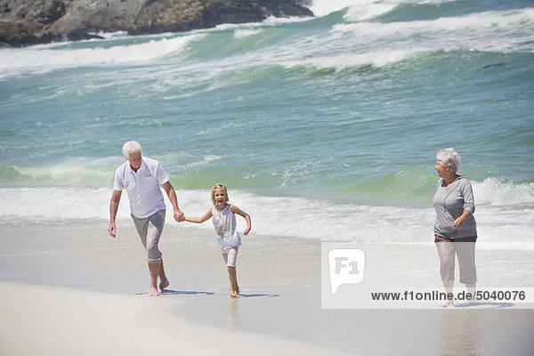 Seniorenpaar mit ihrer Enkelin am Strand