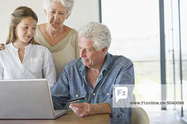 Senior Mann beim Homeshopping mit seiner Familie in seiner Nähe.