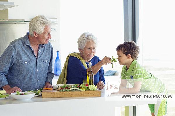 Seniorenpaar mit ihrem Enkel an der Küchentheke