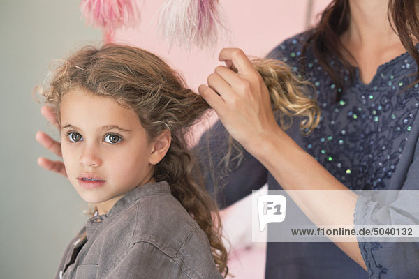 Mutter stylen das Haar ihrer Tochter
