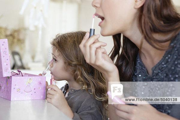 Junge Frau und kleines Mädchen beim Schminken am Frisiertisch