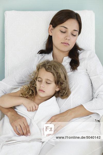 Junge Frau schläft mit kleinem Mädchen in Handtuch gewickelt