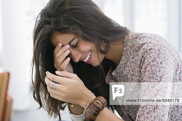 Seitenprofil einer wunderschönen Frau  die mit geschlossenen Augen lächelt.