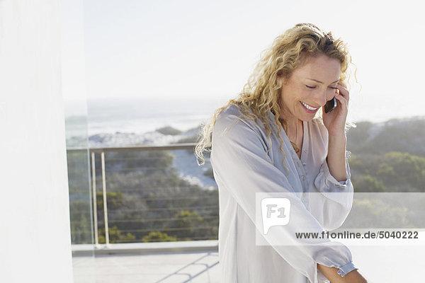 Mittlere erwachsene Frau  die auf einem Handy spricht und lächelt.