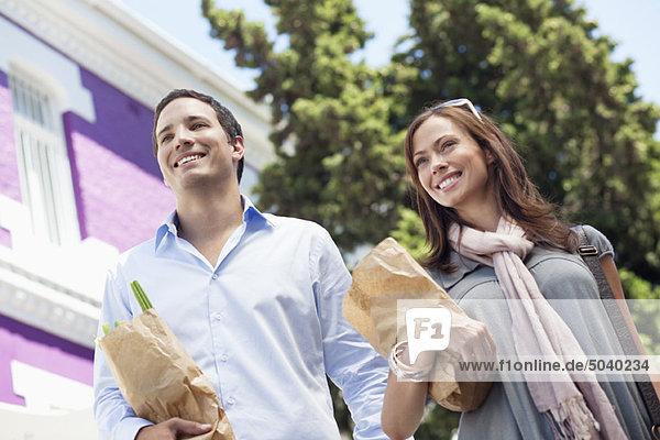 Lächelndes Paar stehend mit Papiertüten voller Gemüse