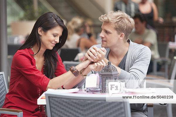 Junger Mann hält die Hand seiner Freundin in einem Restaurant.