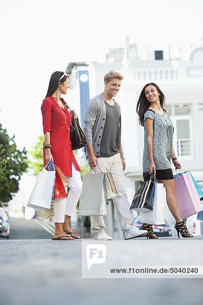 Junger Mann mit zwei Frauen  die mit Einkaufstaschen gehen.