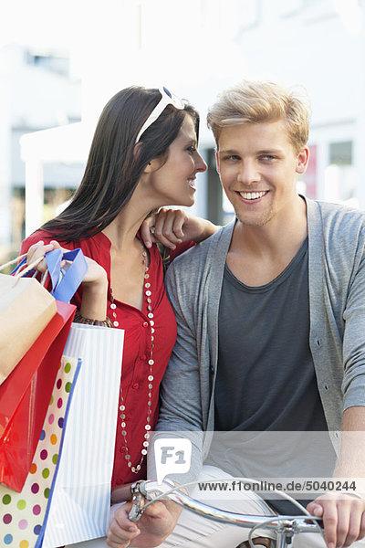 Junger Mann auf dem Fahrrad mit seiner Freundin  die ihm ins Ohr flüstert.