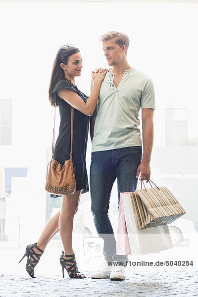 Junges Paar steht zusammen mit Einkaufstaschen