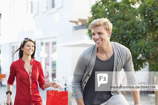 Junger Mann  der mit seiner Freundin mit Einkaufstaschen hinter ihm herrennt.