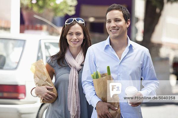 Lächelndes Paar mit Papiertüten voller Gemüse