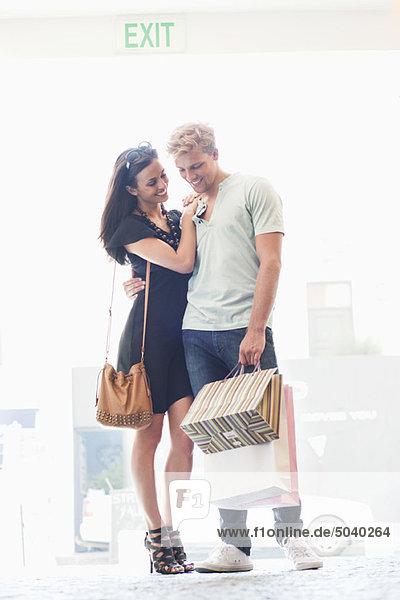 Lächelndes junges Paar stehend mit Einkaufstaschen