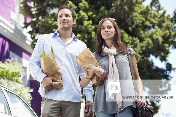 Paar stehend mit Papiertüten voller Gemüse