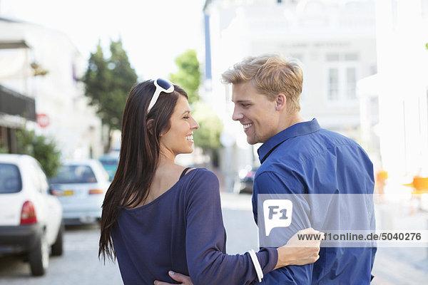 Junges Paar schaut sich an und lächelt.