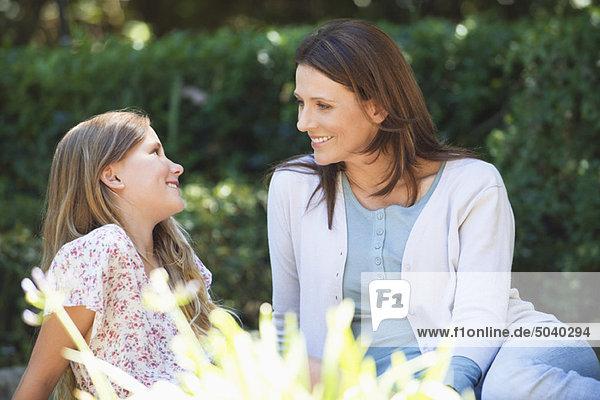 Süßes kleines Mädchen und ihre Mutter sitzen zusammen im Garten.