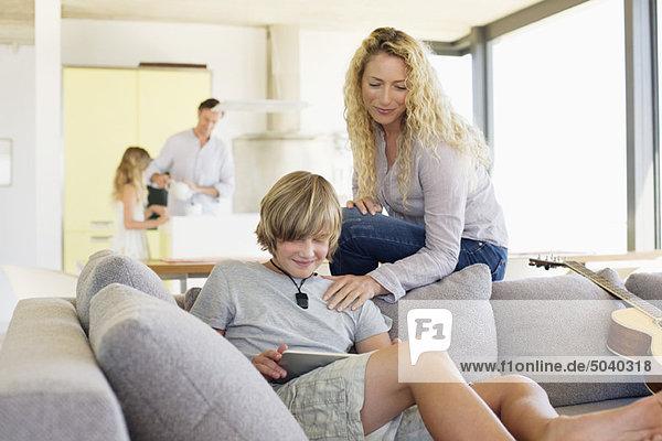 Teenager-Junge  der ein digitales Tablett benutzt  während seine Mutter ihn ansieht.