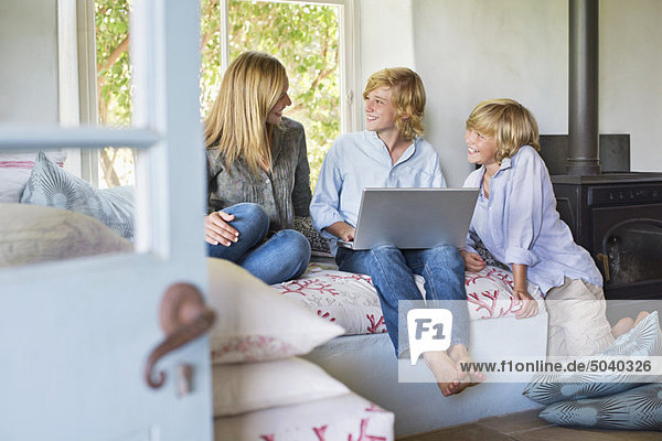Children and their mother using laptop at house
