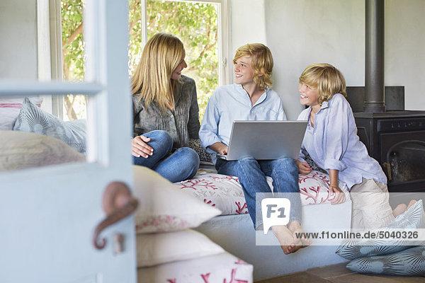 Kinder und ihre Mutter mit Laptop im Haus