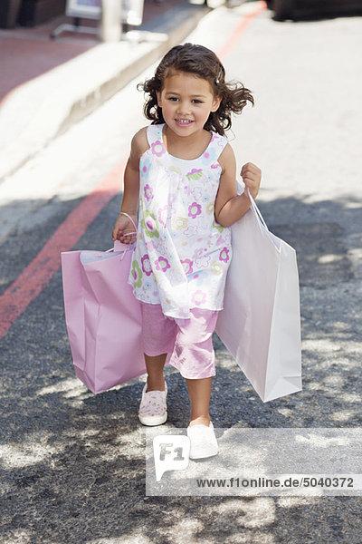 Süßes kleines Mädchen,  das mit Einkaufstaschen in den Händen geht.