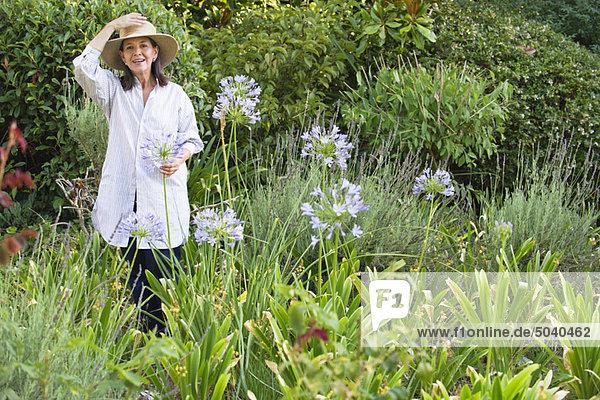 Porträt einer älteren Frau mit Blumen im Garten