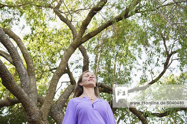 Junge Frau unter einem Baum stehend