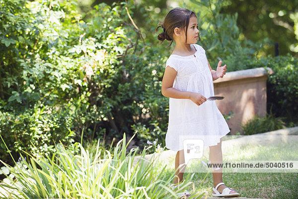 Side profile of a little girl walking in the garden