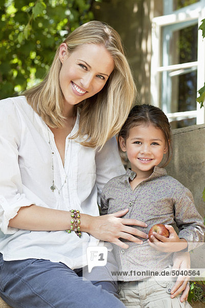 Daughter holding apple with mother smiling