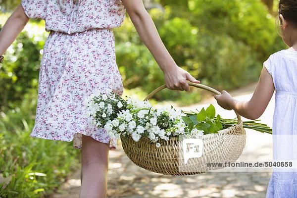 Rückansicht der Geschwister beim Händchenhalten im Garten