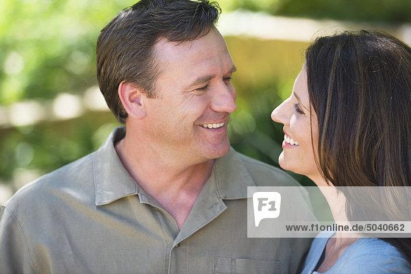 Ein glückliches Paar sieht sich an und lächelt.