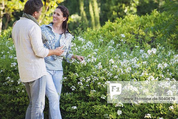 Fröhliches  reifes Paar  das in einem Garten schwelgt.