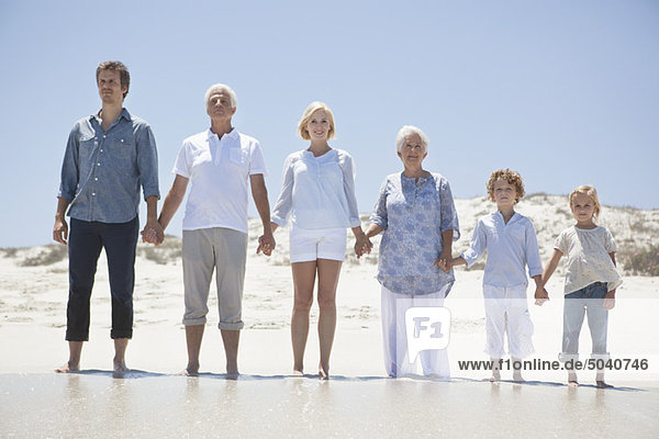 Family standing on the beach