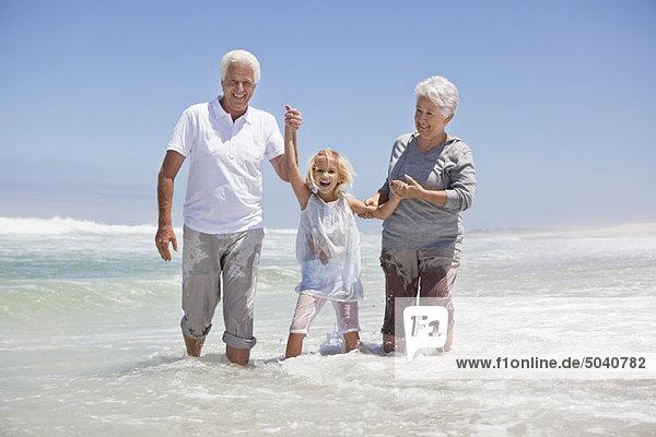 Mädchen genießt am Strand mit ihren Großeltern