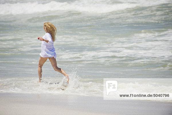 Seitenprofil einer am Strand laufenden Frau
