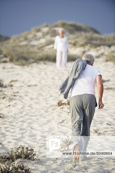 Rückansicht eines älteren Mannes  der auf eine im Hintergrund stehende Frau zu läuft.