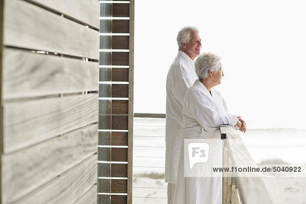 Seniorenpaar auf dem Balkon stehend