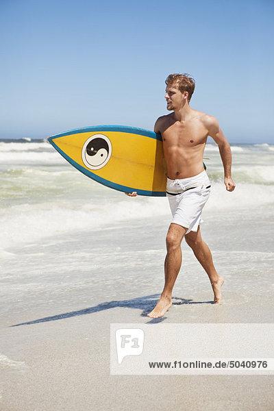 Mann läuft am Strand mit Surfbrett