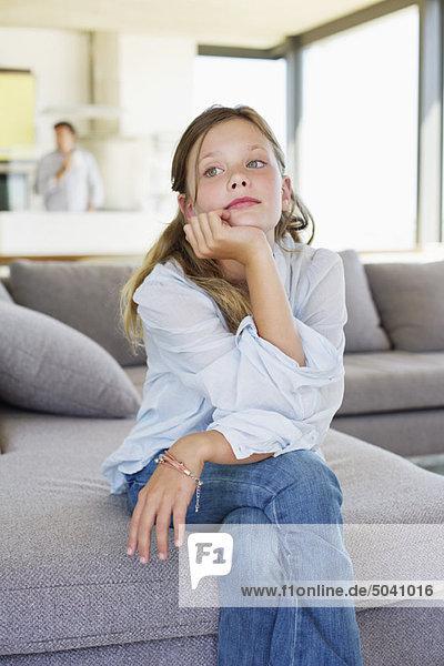 Mädchen auf einer Couch sitzend und nachdenkend
