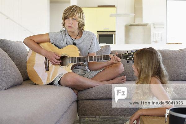 Mädchen sieht einen Bruder an  der Gitarre spielt.