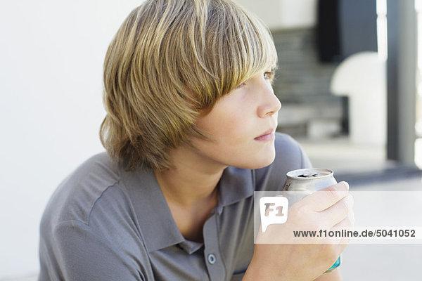Teenager-Junge trinkt zu Hause kaltes Getränk