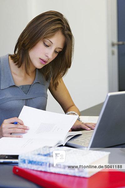 Schöne Frau  die ein Buch liest  während sie den Laptop im Klassenzimmer benutzt.