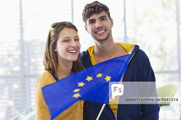 Porträt eines Ehepaares  das auf einem Flughafen die Flagge der Europäischen Union hält.